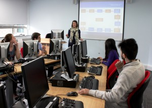 a photo of a person teaching a group of students in a computer room