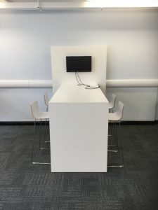 an image of one of the library's flatscreens in front of a group workspace