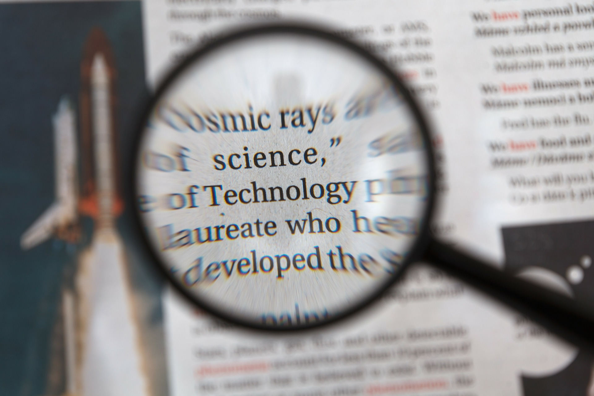 an image of a magnifying glass hovering over a newspaper article