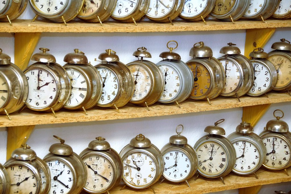 a photo of a collection of alarm clocks sitting on shelves